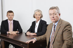 Portrait of confident business group at desk in office Stock Image