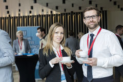 Portrait of confident business people holding coffee cups at lobby in convention center.  stock photos