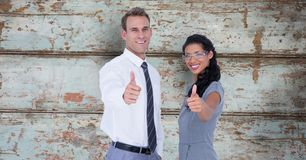 Portrait of confident business people showing thumbs up against wooden wall Royalty Free Stock Photos