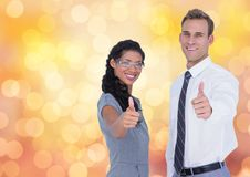 Portrait of confident business people showing thumbs up over bokeh Stock Photos