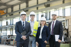 Portrait of confident business people wearing hardhats in metal industry Stock Photos