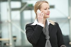 Portrait of a confident business woman on mobile phone. Outdoors Stock Images