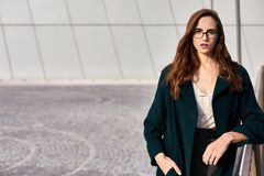 Portrait of a confident business woman wearing glasses in and urban scene. Simple background royalty free stock photo