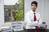 Portrait of a confident businessman with arms crossed looking away in office Royalty Free Stock Photo