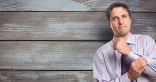 Portrait of confident businessman buttoning sleeve against wooden wall stock photos