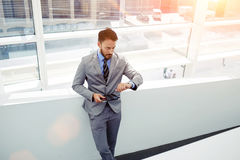 Portrait of a confident businessman dressed in luxury corporate clothing checking time on his watches and holding digital tablet Royalty Free Stock Photos