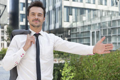 Portrait of confident businessman gesturing while standing outside office building Royalty Free Stock Photos