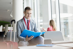 Portrait of confident businessman holding file while sitting at lobby in convention center.  stock photo