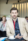 Portrait of confident businessman holding smart phone while sitting at convention center Royalty Free Stock Photos