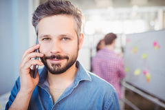 Portrait of confident businessman listening to cellphone at creative office Stock Images