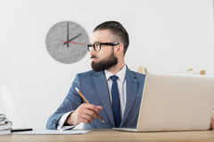 Confident businessman looking away working at workplace with laptop Stock Images