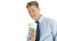 Portrait Of Confident Businessman Showing Euro Banknotes. Portrait of confident mature businessman showing euro banknotes isolated over white background Royalty Free Stock Photos