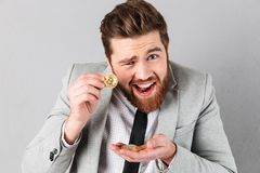 Portrait of a confident businessman showing golden bitcoins Royalty Free Stock Images