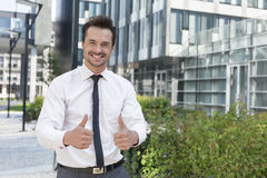 Portrait of confident businessman showing thumbs up outside office building Royalty Free Stock Images