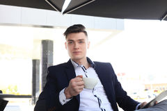 Portrait of a confident businessman sitting on the bench and drinking coffee outdoors. Stock Image