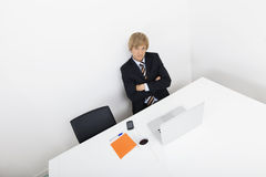 Portrait of confident businessman sitting at desk with laptop Royalty Free Stock Images