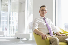 Portrait of confident businessman sitting at office lobby Stock Photo