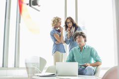 Portrait of confident businessman sitting at table with female colleagues conversing in background Royalty Free Stock Images