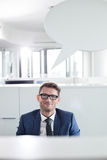 Portrait of confident businessman with speech bubble in office Royalty Free Stock Photography