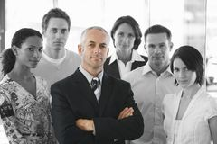 Portrait of a confident businessman standing arms crossed with office workers Stock Photography