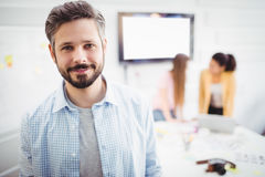 Portrait of confident businessman standing in meeting room at creative office Royalty Free Stock Photo