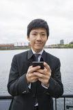 Portrait of confident businessman text messaging through cell phone outdoors Royalty Free Stock Photo