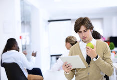 Portrait of confident businessman using digital tablet while colleague in background Stock Photos