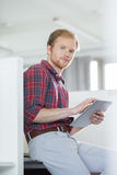 Portrait of confident businessman using tablet PC in creative office Royalty Free Stock Photo
