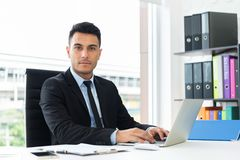 Portrait of a confident businessman working on laptop. royalty free stock images