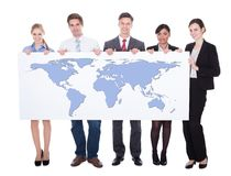 Portrait of confident businesspeople holding worldmap. Full length portrait of confident businesspeople holding worldmap against white background. Source of royalty free stock photos