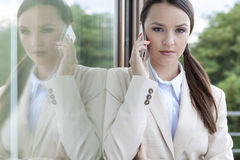 Portrait of confident businesswoman answering cell phone by glass door Royalty Free Stock Images