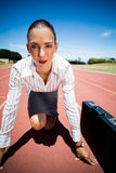 Portrait of confident businesswoman with briefcase in ready to run position. On running track Royalty Free Stock Image