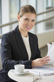 Portrait of confident businesswoman with documents sitting at office cafe Stock Photography