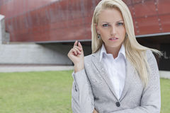 Portrait of confident businesswoman gesturing against office building Stock Images