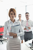 Portrait of confident businesswoman holding book with colleagues in background at office Stock Photography