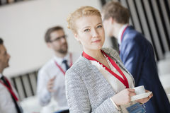 Portrait of confident businesswoman holding coffee cup at lobby in convention center.  Stock Images