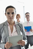 Portrait of confident businesswoman holding digital tablet with colleagues in background at office Royalty Free Stock Photography