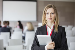 Portrait of confident businesswoman holding digital tablet in seminar hall.  royalty free stock images