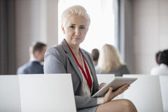 Portrait of confident businesswoman holding digital tablet while sitting in seminar hall Stock Photo