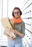 Portrait of confident businesswoman holding envelopes in locker room at creative office Royalty Free Stock Image