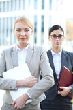Portrait of confident businesswoman holding laptop with colleague in background Stock Image