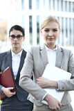Portrait of confident businesswoman holding laptop with colleague in background Stock Photos