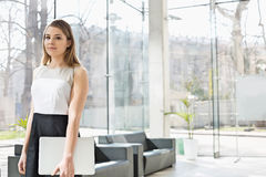Portrait of confident businesswoman holding laptop while standing at office lobby Stock Image