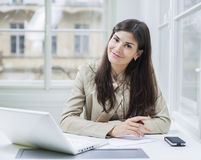 Portrait of confident businesswoman with laptop sitting at office desk Stock Photography