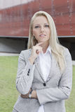 Portrait of confident businesswoman standing against office building Stock Photography
