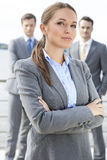 Portrait of confident businesswoman standing arms crossed with coworkers in background on terrace Royalty Free Stock Photos