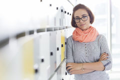 Portrait of confident businesswoman standing arms crossed in locker room at creative office Royalty Free Stock Photos