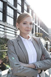 Portrait of confident businesswoman standing arms crossed outside office building Stock Image