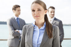 Portrait of confident businesswoman standing with coworkers in background on terrace Royalty Free Stock Photography