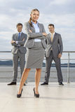Portrait of confident businesswoman standing with coworkers on terrace against sky Royalty Free Stock Photo